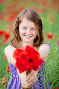 Beautiful little girl with red flowers Stock Photos