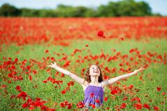 laughing young girl in a poppy field - stock photo
