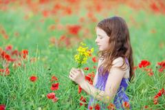 Little girl smelling a bunch of flowers Stock Photos