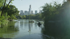 People in rowboats on central park lake with the New York skyline behind them. - stock footage