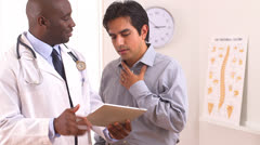 African American doctor using tablet pc with Hispanic patient Stock Footage