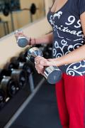 young woman using dumbbells in a gym - stock photo