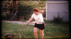 Woman cuts grass in backyard, 233 vintage film home movie Stock Footage