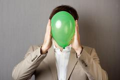 businessman holding balloon in front of face - stock photo
