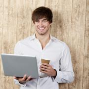 businessman with disposable cup and laptop - stock photo