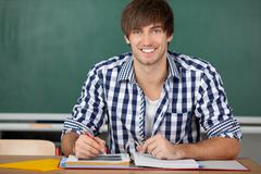 male student with binder sitting at desk - stock photo