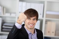 Businessman with clenched fist in office Stock Photos