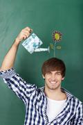 Male student holding watering can with flower drawn on chalkboar Stock Photos