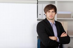 businessman with arms crossed in front of flip chart - stock photo