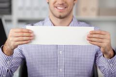young businessman holding a white paper - stock photo