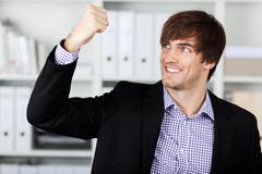 Businessman with clenched fist celebrating victory in office Stock Photos