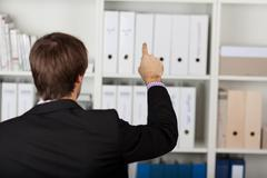 Businessman pointing at invisible screen Stock Photos