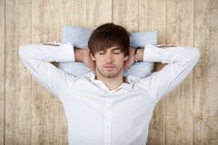 businessman with hands behind head sleeping on wooden wall - stock photo