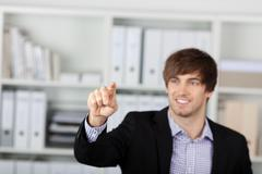 Businessman pointing at invisible screen in office Stock Photos