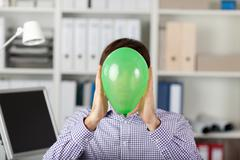 Businessman holding balloon in front of face Stock Photos