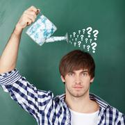 student holding watering can with question marks on chalkboard - stock photo
