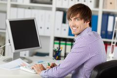 handsome young businessman smiling at desk - stock photo