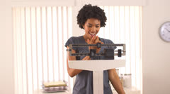 Black woman excited about weight loss on scale - stock footage
