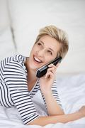 woman using cordless phone while looking up in bed - stock photo