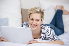 Woman holding digital tablet while lying on bed Stock Photos