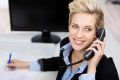 woman using phone while looking up in office - stock photo