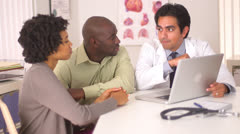Hispanic doctor talking to African American couple with laptop computer - stock footage