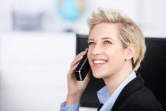 Woman using cordless phone while looking up in office Stock Photos
