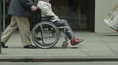 Elderly lady in a wheelchair being pushed along a crowded city street Stock Footage