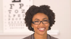 African American woman wearing glasses at optometrist - stock footage