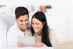 Young couple using a tablet in their living room Stock Photos