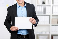 Smiling businessman showing a blank sheet Stock Photos