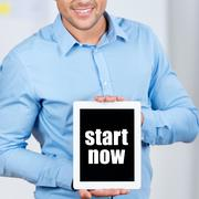 businessman holding digital tablet with start now sign - stock photo