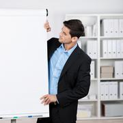 businessman wearing suit looking at flipchart - stock photo