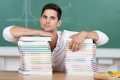 serious student with piles of textbooks - stock photo
