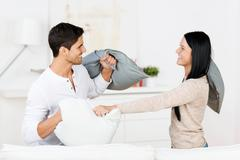 Couple having pillow fight in house Stock Photos