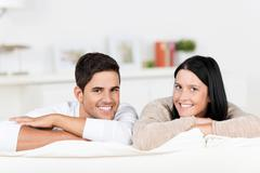 Happy couple leaning on sofa at home Stock Photos