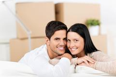 Couple leaning on sofa with cardboard boxes in background Stock Photos