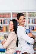 Students holding binders while standing back to back in library Stock Photos