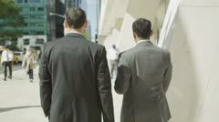 Anonymous business men chat together as they walk along a Manhattan street Stock Footage