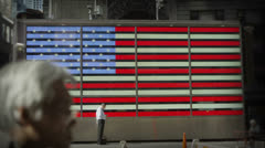 A man stands in front of an electronic representation of the American flag Stock Footage