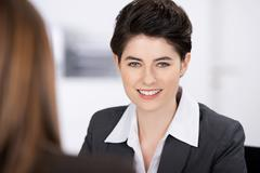 Stock Photo of smiling businesswoman with coworker in foreground