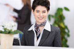 beautiful female receptionist welcoming with smile - stock photo