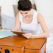 woman with suitcase searching for travel destination on digital - stock photo