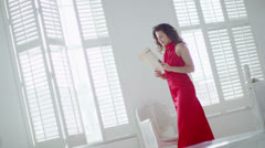 Beautiful woman in evening gown returns home and takes off her shoes Stock Footage
