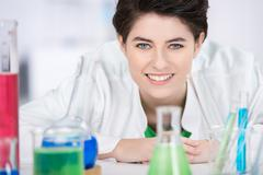 Female scientist with chemicals on foreground in laboratory Stock Photos