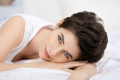 Woman with blue eyes lying on bed Stock Photos