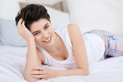 Smiling woman lying on the bed to relax Stock Photos