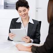 businesswoman using digital tablet with coworker - stock photo
