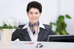 confident receptionist smiling at counter - stock photo