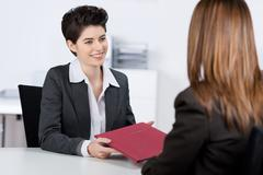 candidate giving file to businesswoman at desk - stock photo